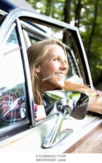 Happy young woman in car in forest