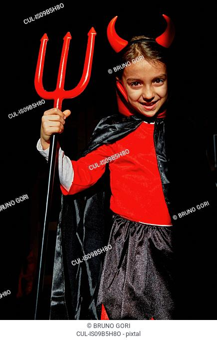 Portrait of girl dressed up as a devil holding a devil's fork