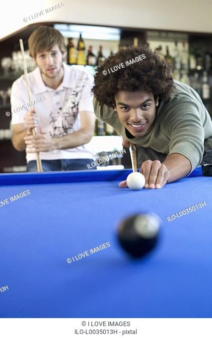 Two young men playing pool