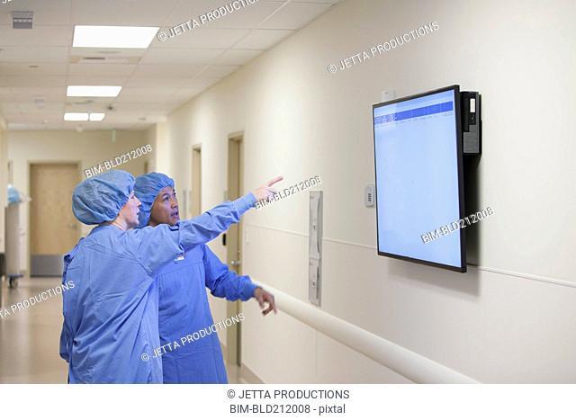 Surgeons watching monitor in hospital corridor