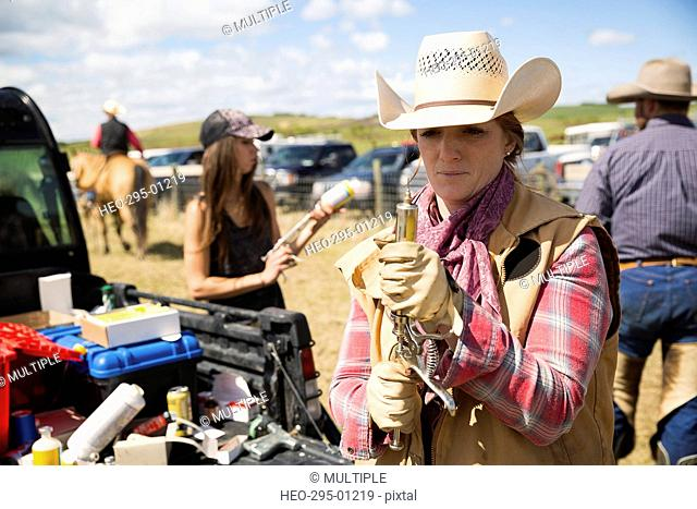 Female cattle rancher preparing injection