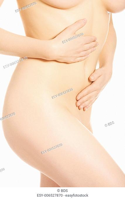 Beautiful nude fit woman body with hand on belly, isolated on white