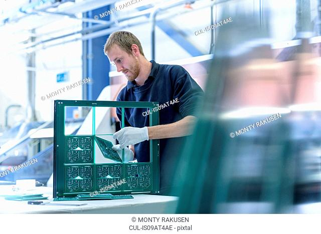 Worker cutting circuit boards in circuit board factory