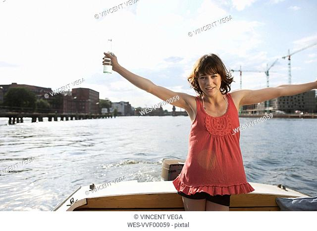 Germany, Berlin, Young woman on motor boat, arms outstretched