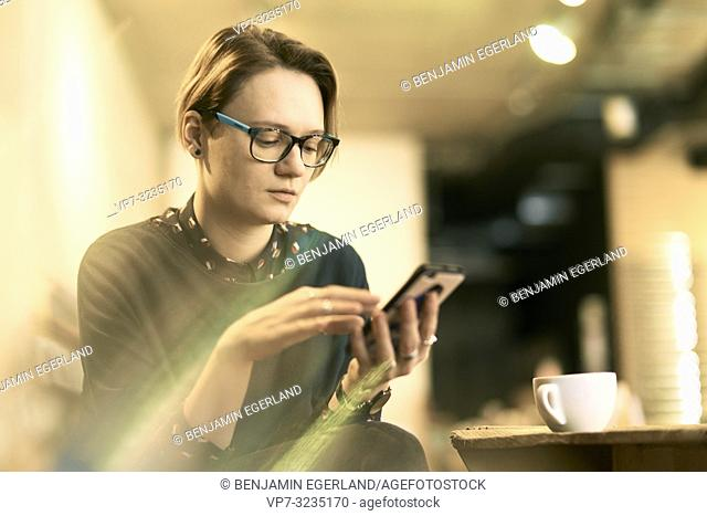 woman using phone indoors in coffee shop, in Munich, Germany