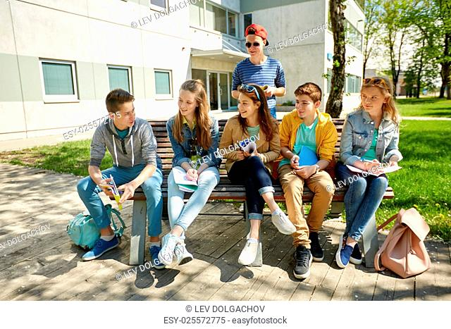 education, high school and people concept - group of happy teenage students with notebooks learning at campus yard