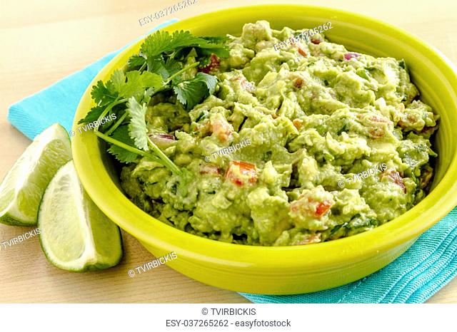 Close up of homemade chunky guacamole in bright green bowl sitting on blue napkin with lime wedges