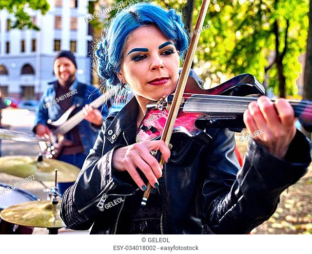 Music street performers girl violinist with blue hair playing in city park outdoor