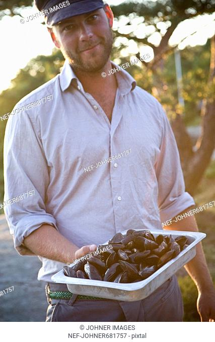 Man holding a tray with sea mussels, Sweden