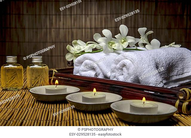 3 candles, towels, orchid and oil bottles