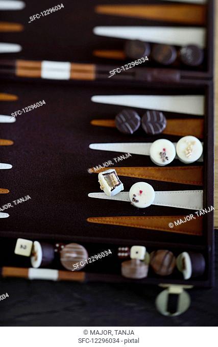 Various chocolates on a backgammon board
