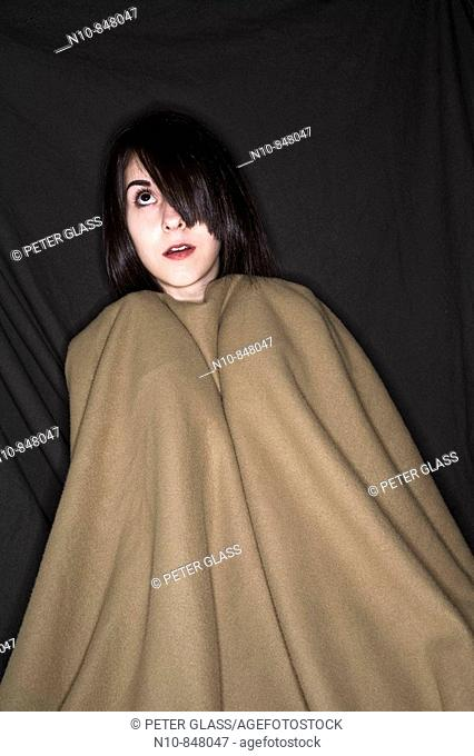 Young woman wrapped in a blanket