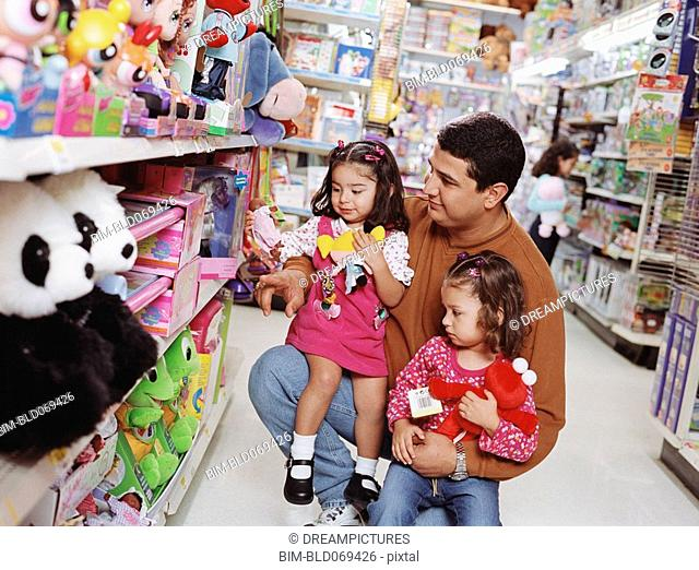 Hispanic father and young daughters at toy store