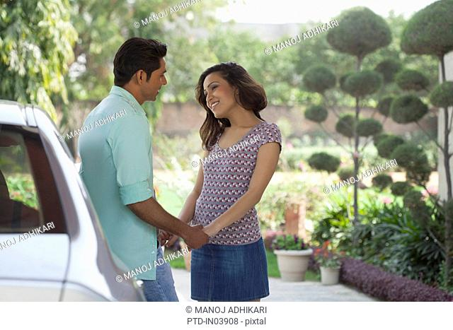 India, Man and woman holding hands standing next to car