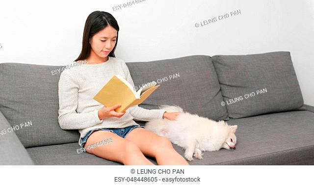 Young Woman reading book with her dog at home