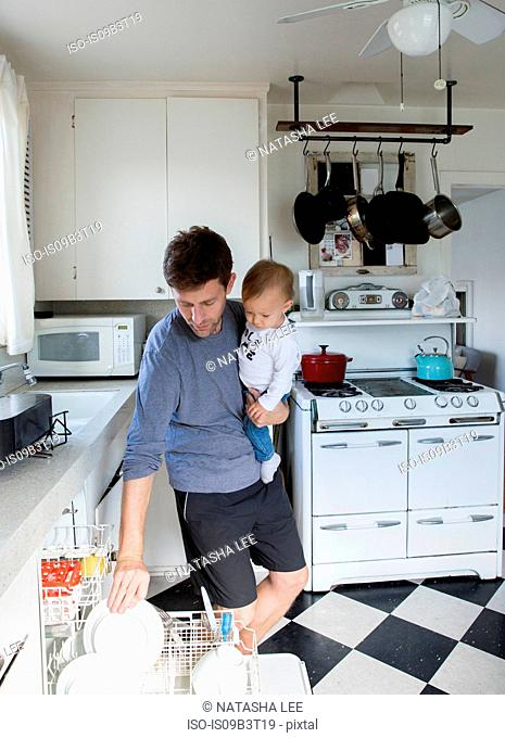 Father and young son in kitchen, father holding son whilst putting dishes in dishwasher