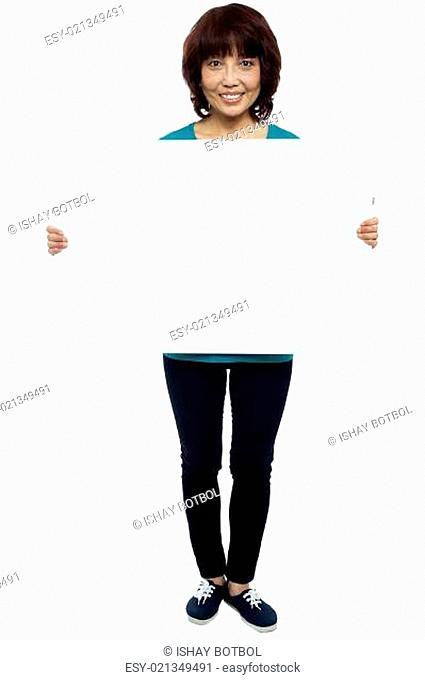 Asian female model cheerfully holding blank billboard