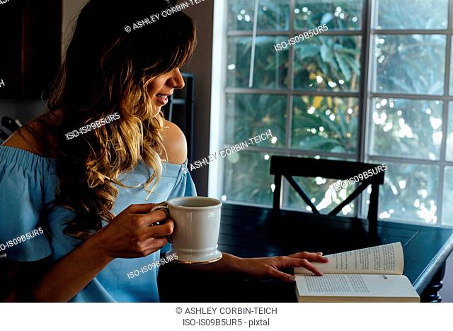 Young woman reading book at table