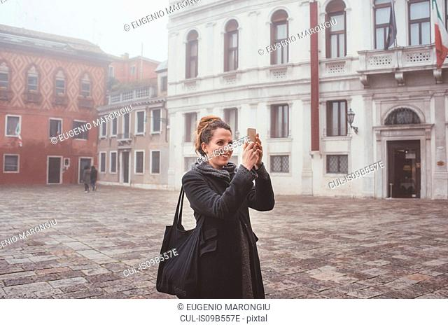 Young woman taking smartphone selfie in misty square, Venice, Italy