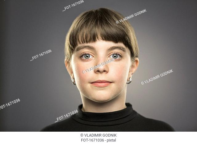Portrait of smiling girl with gray eyes against gray background