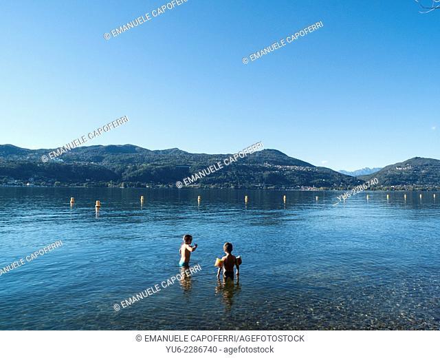 Children bathe in the lake Maggiore, Ranco, Lombardy, Italy