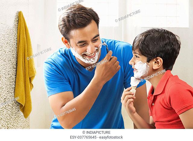 Boy applying shaving cream with father