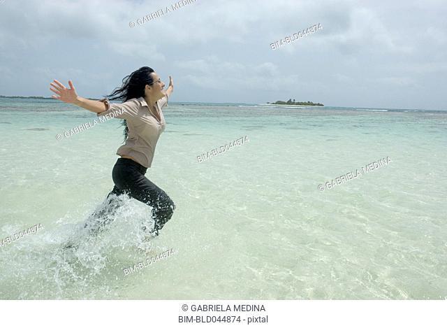 Hispanic businesswoman running in water