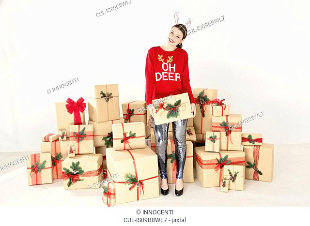 Young woman in red sweater and reindeer antlers by stacked christmas gifts holding christmas parcel