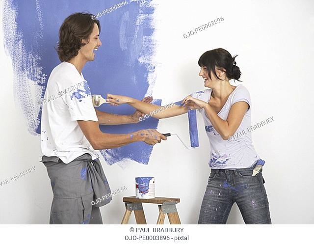 Man and woman playing with paint and laughing
