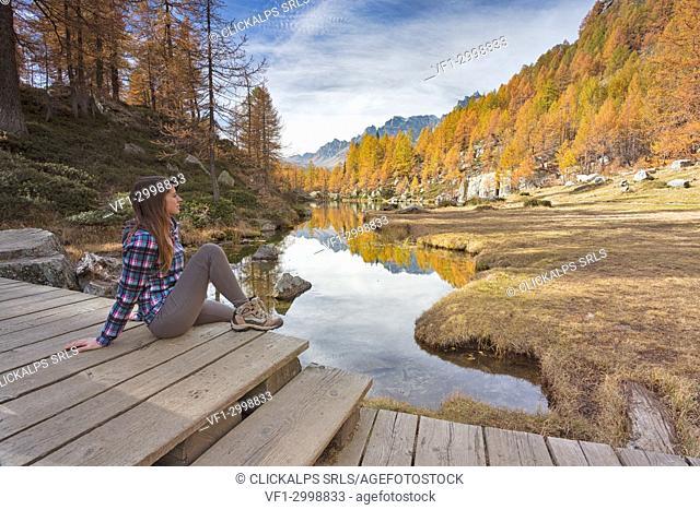 A woman staring at the small lake near Crampiolo known as Witches Lake, Alpe Veglia and Alpe Devero Natural Park, Baceno, Verbano Cusio Ossola province
