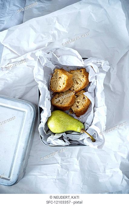 A lunchbox containing a pear and four pieces of vegan pear cake made of spelt and cornflour, sweetened with coconut blossom sugar