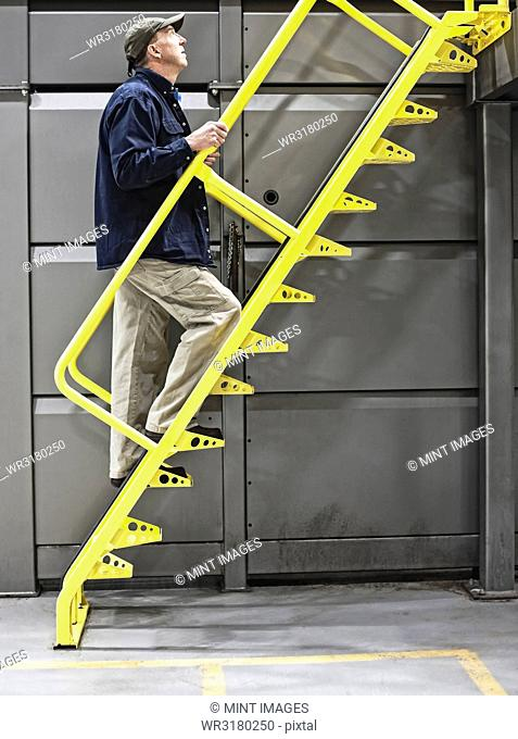 Warehouse worker climbing a metal staircase in a warehouse facility for bottled water