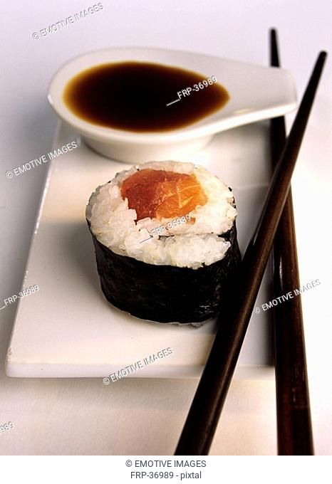 Maki sushi with salmon, soy sauce and chopsticks
