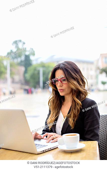Business woman with laptop in a Cafe