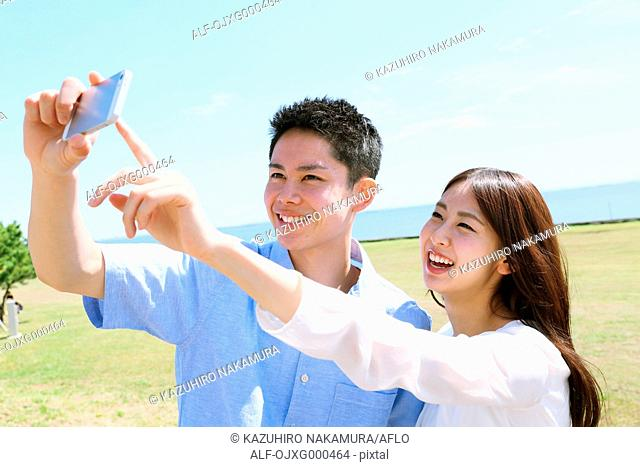 Young Japanese couple taking selfie by the sea