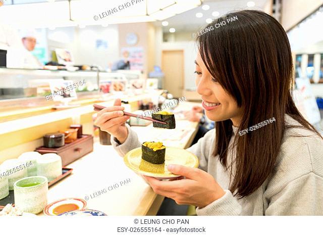 Woman having sushi in restaurant