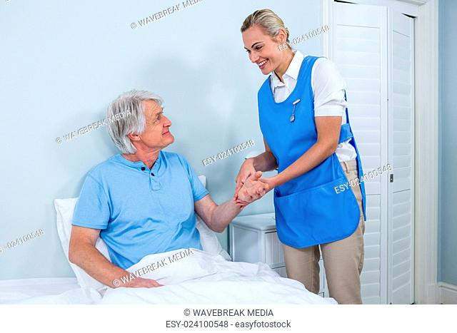 Nurse holding senior man hand in hospital