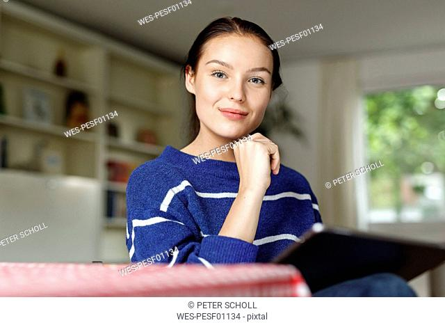 Young woman sitting at home, using digital tablet