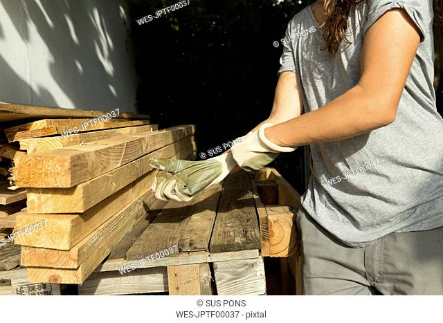 Craftswoman putting on protective gloves at a pile of wood