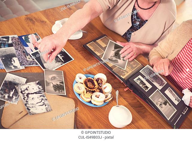 Overhead view of two senior women looking at old photographs at table