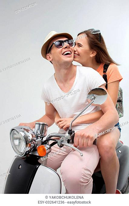 I love you. Portrait of pretty young loving couple sitting on scooter. The woman is kissing male cheek with gentleness and smiling. Isolated