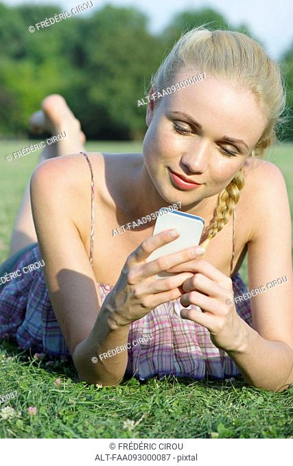Woman lying on grass, using smartphone