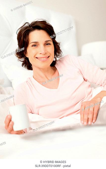 Smiling woman reading newspaper in bed