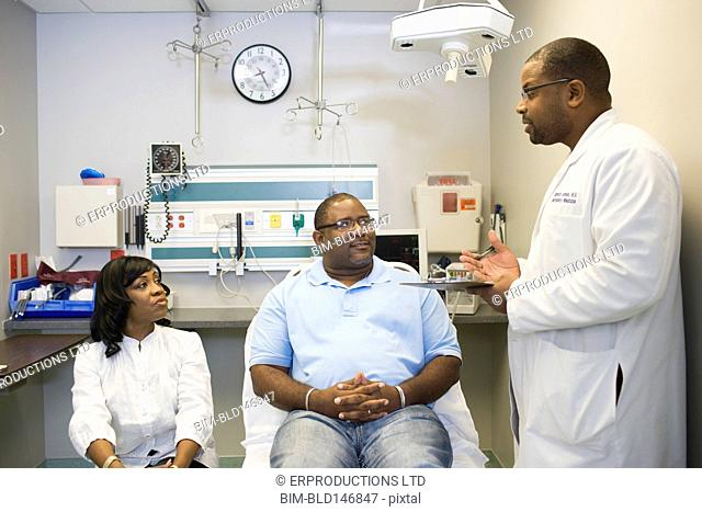 African American doctor talking to patient and his wife in hospital