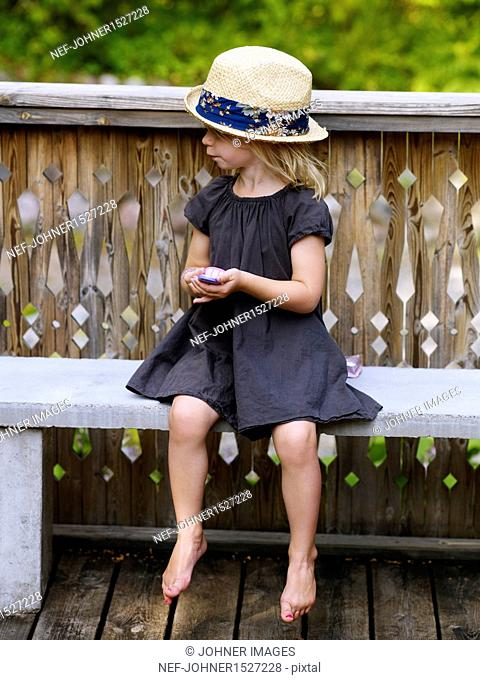 Girl wearing straw hat sitting on bench with toy phone