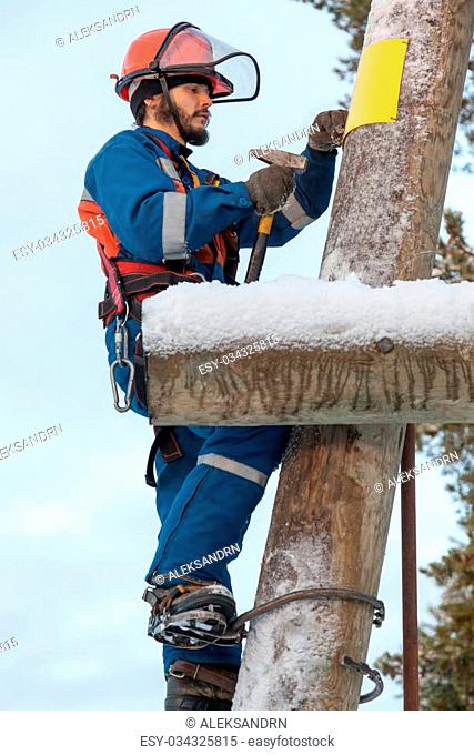 Electrician in blue overalls working on a power line pole in winter