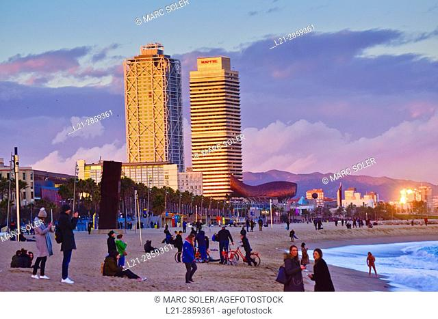 People at Barceloneta beach at dusk. At the bottom, Hotel Arts building and Mapfre tower building. Barceloneta quarter, Barcelona, Catalonia, Spain