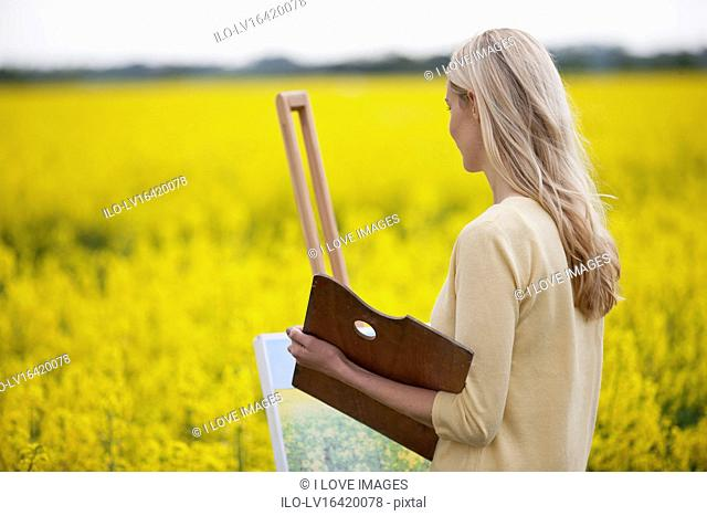 A young woman painting a picture of a rape seed field in flower, looking at the field