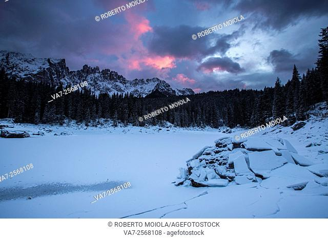 Sunset at Lake Carezza covered with snow in the background the Latemar group. Ega Valley. Dolomites. Trentino Alto Adige Italy