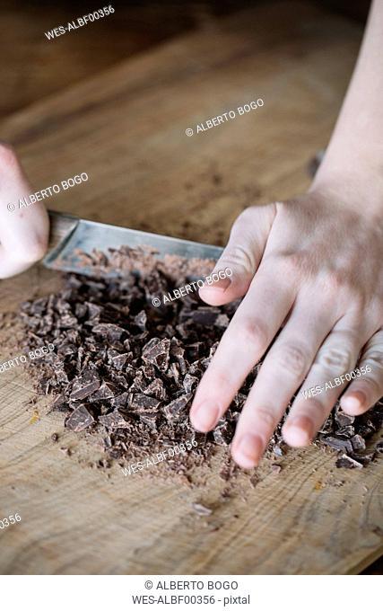Woman's hand chopping bitter chocolate, close-up